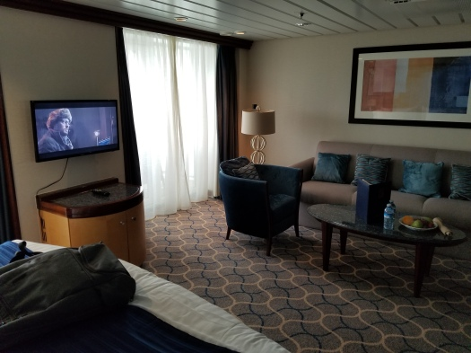 The couch, television, and door leading to the balcony in Grand Suite 1298 on the Liberty of the Seas.